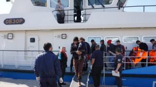 Migrants disembark a Bulgarian vessel