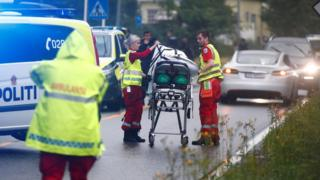 Emergency crews are seen near a stretcher after a shooting in the Al-Noor Islamic Centre mosque, near Oslo, on 10 August
