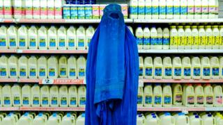 A woman wearing a bright blue burka stands against bottles of milk in a supermarket.