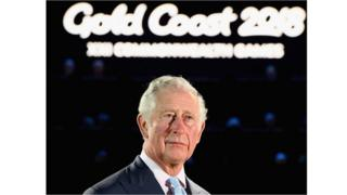 Prince Charles reads out the Queen's message underneath a sign that says 'Gold Coast 2018'.