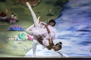 A male and female ballet dancer perform a complex lift on stage.
