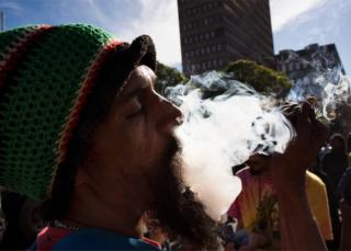 A man smokes marijuana out of a bottle-neck pipe, joining about 1500 people as they protest in front of the South African Parliament, to call for the complete legalisation of Cannabis or Marijuana in South Africa, on May 5, 2018, in Cape Town
