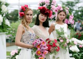 Three models wearing bridal designs by Alan Hannah hold bouquets of peonies in the Great Pavilion during the press day for this year's RHS Chelsea Flower Show