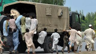 Pakistani flood victims struggle for relief bags being distributed in Nowshera on August 20, 2010.