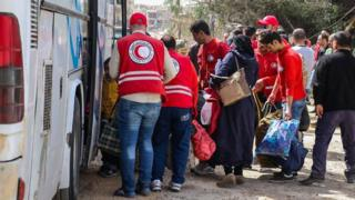 Syrian Arab Red Crescent workers help civilians being evacuated from the rebel-held town of Harasta, in the Eastern Ghouta, on to buses (22 March 2018)