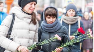 Люди несут цветы к месту пожара