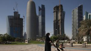 A woman pushes a pram near new office skyscrapers in the financial district in Doha,