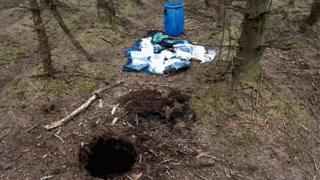 A hole in the ground in the forest with the weapon that had been stored inside
