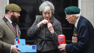 Prime Minister Theresa May attaches a poppy to her jacket