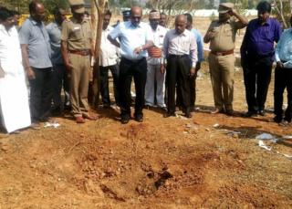 Indian authorities inspect the site of a suspected meteorite landing on February 7, 2016 in an impact that killed a bus driver and injured three others on February 6