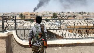 Un combatiente kurdo observa Raqqa justo después de un ataque aéreo sobre la ciudad.