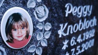 a photograph of a little blonde haired-blue-eyed girl on a grave headstone reading Peggy Knobloch 1992-2001