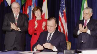 US President George Bush caps his pen after signing the North American Free Trade Agreement at the Organization of American States headquarters, 17 December 1992, in Washington D.C.. Looking on are Mexican Ambassador Gustavo Petricioli (L), US Trade Representative Carla Hills and Canadian Ambassador Derek Burney (R)