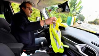 Philippe Salmon holds up a yellow vest in his car in Saint-Vivien-de-Medoc, near Bordeaux, south-western France, 14 November