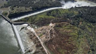 Water flows over the emergency spillway at Lake Oroville for the first time in the nearly 50-year history of the Oroville Dam, 11 February 2017