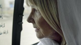 Maureen Bacon looks out of bus window at Basra, where her son died