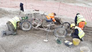 Archaeologists excavating car
