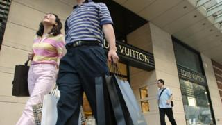 Chinese shoppers walk past a Louis Vuitton store