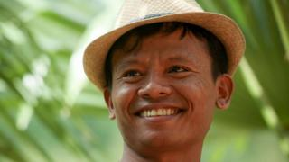 Lawi Weng, smiling and wearing a hat