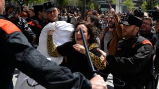 A protester breaks through a police line after a nine-year sentence was given to five men accused of the multiple rape of a woman