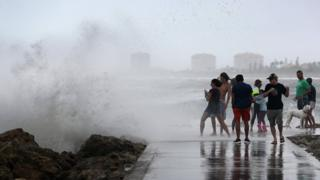 A wave crashes ashore as people enjoy the wind and waves kicked up by Tropical Storm Isaias as it passes through at Jetty Park on August 02, 2020 in Fort Pierce, Florida.