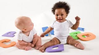 Two babies playing with letters