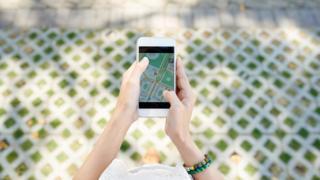 Pedestre procurando o caminho por meio de app