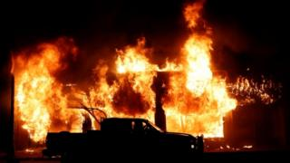 in_pictures A car is seen in front of a fire during a demonstration against the death in Minneapolis