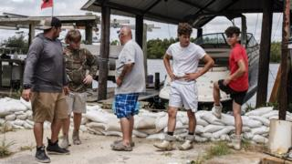 Volunteers inspect a line of sand bags in Jean Lafitte, Louisiana