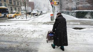 Idosa atravessa a rua em meio a neve