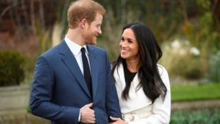 Harry e Meghan Markle sorrindo e olhando um para o outro, em um jardim