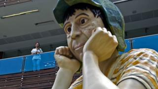 Mulher olha de um mezanino para uma estátua do chaves em um shopping