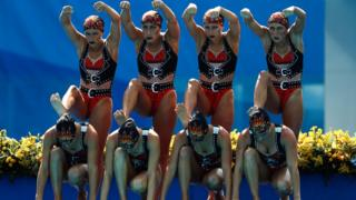 Brazilian women sport black and red ornamental bikinis as they prepare to dive at the synchronised swimming competition at the 2016 Rio Olympics.
