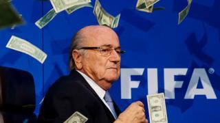 Sepp Blatter entouré de billets en dollars qui lui étaient lancés par le comédien Simon Brodkin lors d'une conférence de presse au siège de la FIFA le 20 juillet 2015 à Zurich.