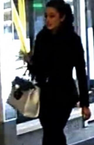 CCTV image of a woman walking with a handbag on her right arm