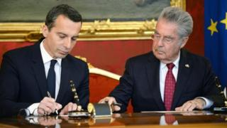 Austria's new chancellor Christian Kern signs the swearing-in documents as chancellor next to outgoing President Heinz Fischer