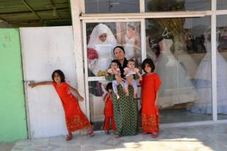 Rozhin and children outside the salon-cum-gown-hire shop