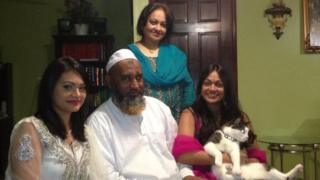 Mr Monir with his two daughters, wife and cat in family photograph