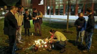 People light candles and lay down flower after a masked man wielding what looked like a sword stabbed four people at a school in Trollhattan, Southern Sweden, 22 October 2015.