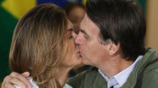 Michelle y Jair Bolsonaro se besan después de votar.