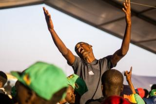 Mourners sing and dance in the early hours following a vigil for late former Zimbabwe President Robert Mugabe at the homestead in Kutama village on 17 September 2019