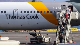 Tourists board a Thomas Cook plane at the airport of Heraclion, Crete