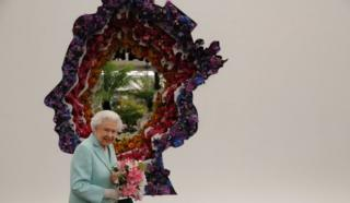 Britain's Queen Elizabeth II is pictured beside a floral exhibit by the New Covent Garden Flower Market, which features an image of the Queen, during a visit to the 2016 Chelsea Flower Show