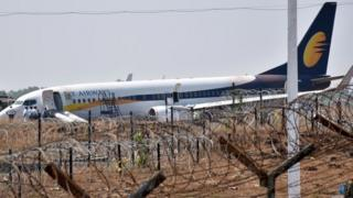 Indian officials gather beside a Jet Airways Boeing 737 aircraft after it skidded off the runway following an aborted take-off at the Goa Airport in Dabolim, in India's western state of Goa (27 December 2017)