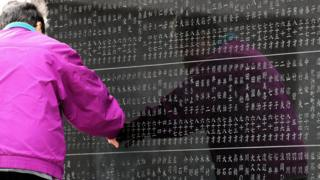 A woman in the city of Sendai touches the names of her relatives on a cenotaph on March 11, 2017, the sixth anniversary of the earthquake, tsunami and nuclear disasters in northeastern Japan.