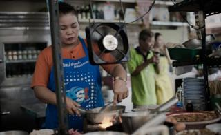 A woman works in restaurant kitchen in Thailand