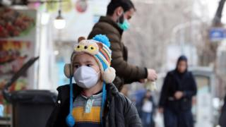 A child wearing a face mask walks in a Tehran street on February 26, 2020