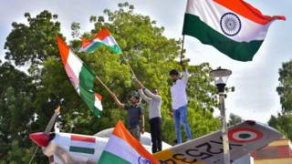 Indian residents hold flags on a model of a military plane to celebrate the air strike launched on February 26, 2019