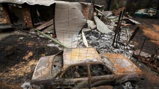 The charred stays of a automobile and a residence following a bushfire in Kinglake in Victoria