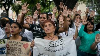 """Hands of a protester depict the message """"No more"""", as a group of people protest in front of the Jose Manuel de los Rios Children's Hospital claiming there is a lack transplants and medical treatments, in Caracas, Venezuela, 27 May 2019."""